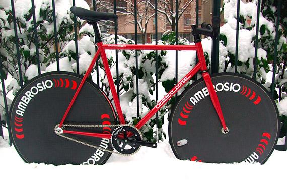 Красный fixed gear, трековый велосипед с карбоновыми колесами на снегу