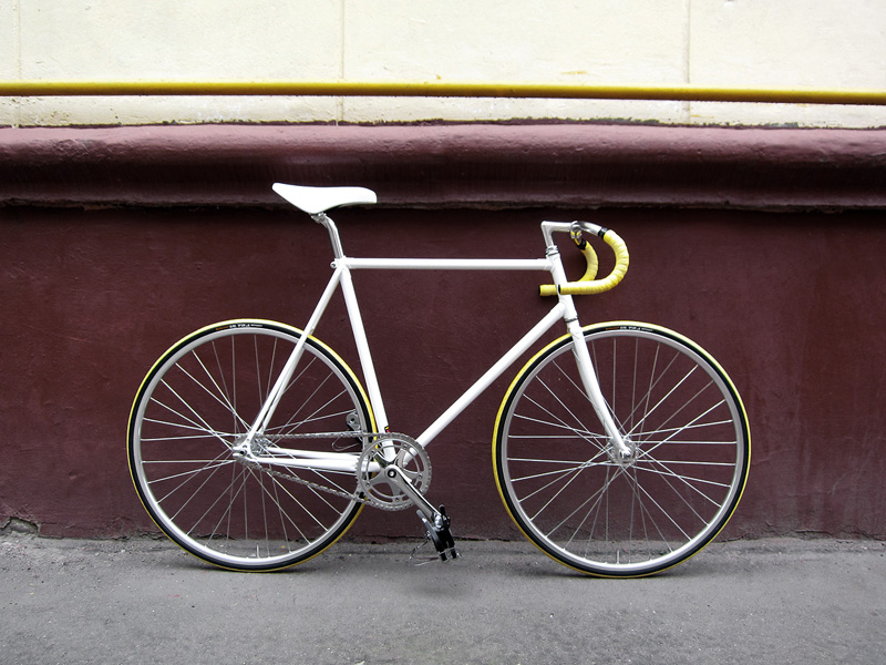 Белый и желтый fixed gear велосипед, который купили в нашем магазине.